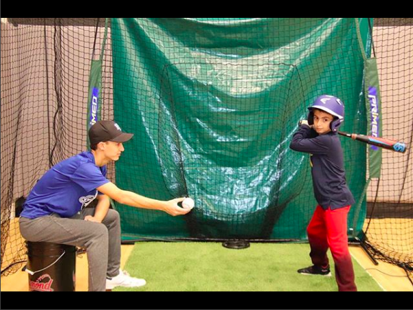 Parky Bondy, President of Talenthood's North Shore Region and a baseball instructor helps a kid with his swing.