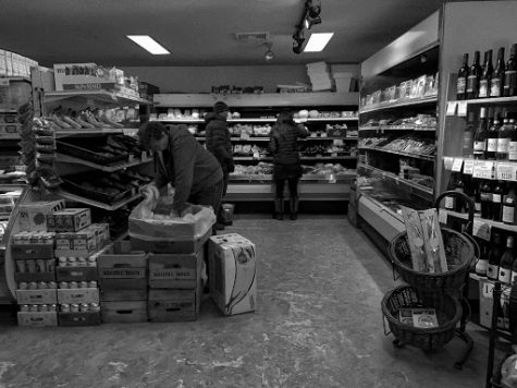 An essential worker stacking the shelves as shoppers lurk through the aisles.