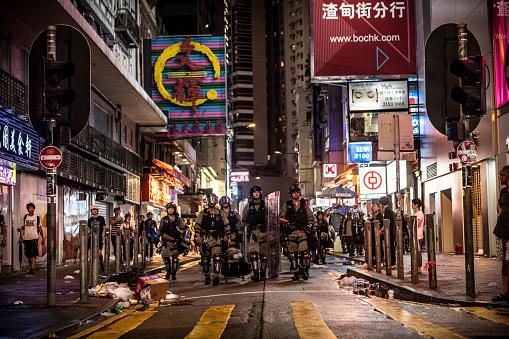 Hong Kong riot police walk together down a road near Causeway Bay MTR station on Hong Kong Island (August 31, 2019)