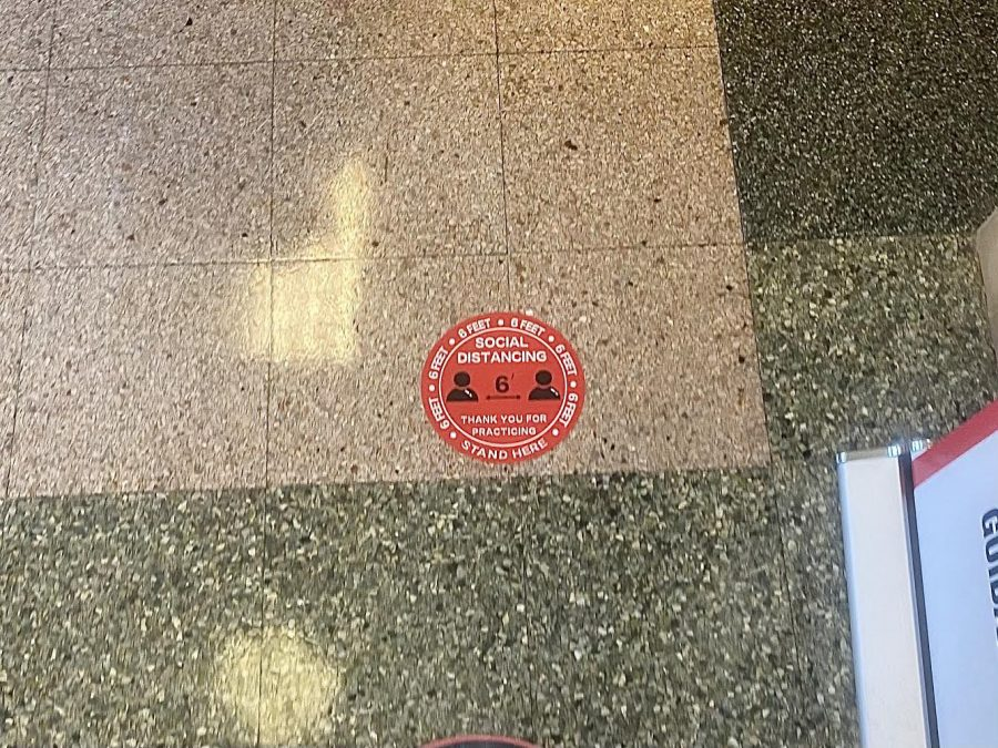 A sticker reminding students to remain socially distant while walking throughout the hallways.