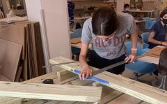 SHS student cutting wood to contribute to new wooden tables for the SHS student body.